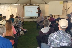 workshop presenter teaching energy fair attendees inside workshop tent